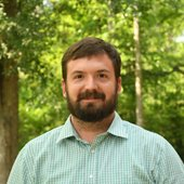 Greg Trotter standing among trees.