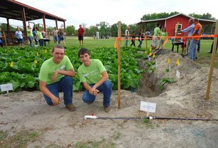 High school agriculture students kneeling in front of the crops with a new irrigation system.