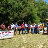 """Individuals posing in front of a red ribbon with a sign saying """"thank you"""" to the Suwannee River Water Management District."""