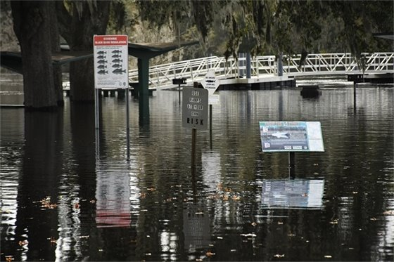 Boat ramp, picknic tables and signs under water due to flooding.