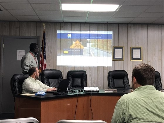 District staff presenting a presentation about the FEMA flood mapping initiative at city hall with a tentative audience.